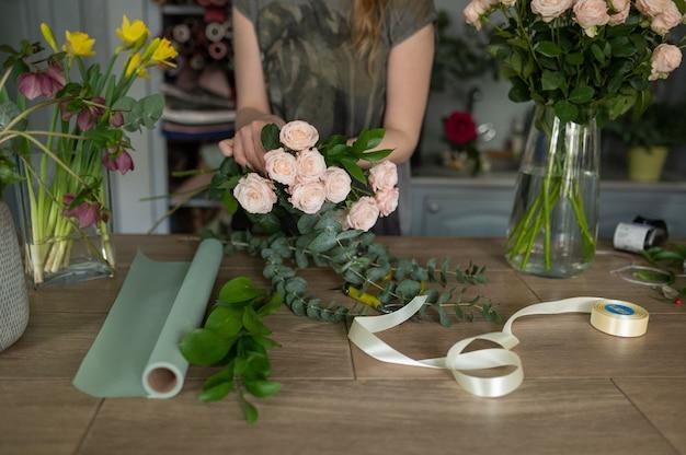 La ragazza del fiorista fa un mazzo. negozio di fiori.