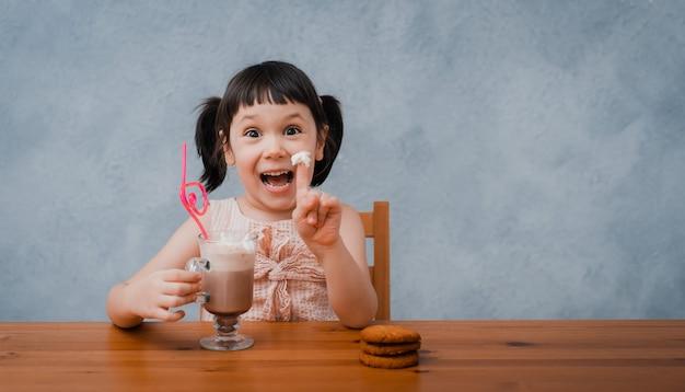 La ragazza del piccolo bambino beve la cioccolata calda o il cacao con i biscotti attraverso un tubo del cocktail su un gray