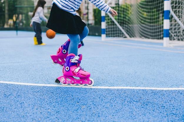 La ragazza del raccolto guida i pattini a rotelle su campo sportivo