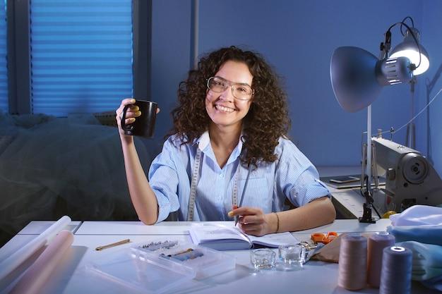 La ragazza del sarto moro con i vetri sorride ed esamina la macchina fotografica