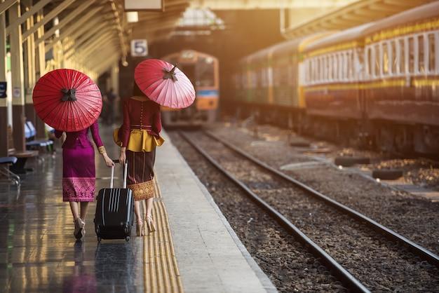 La ragazza del viaggiatore che cammina e aspetta il treno sulla piattaforma ferroviaria