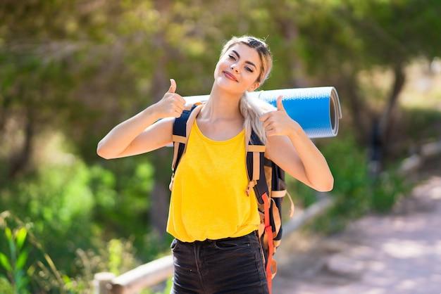 La ragazza dell'adolescente che fa un'escursione all'aperto con i pollici aumenta il gesto e sorridere