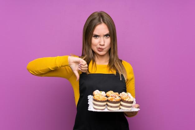 La ragazza dell'adolescente che tiene i lotti di mini torte differenti sopra la porpora isolata mostra il pollice giù firma