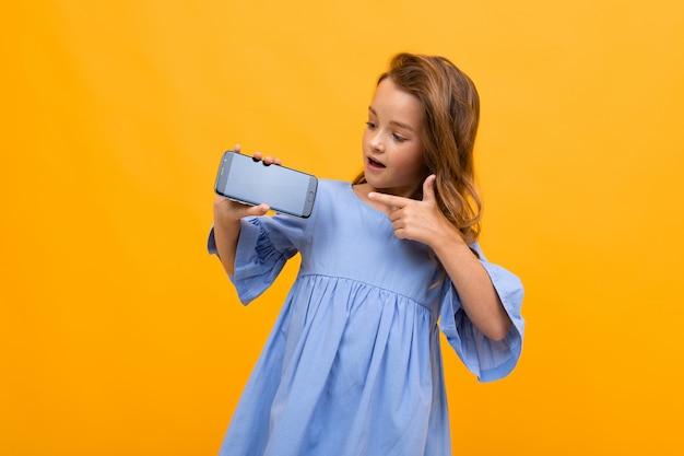 La ragazza dell'adolescente in un vestito blu tiene il telefono orizzontalmente con una disposizione per il sito su un giallo