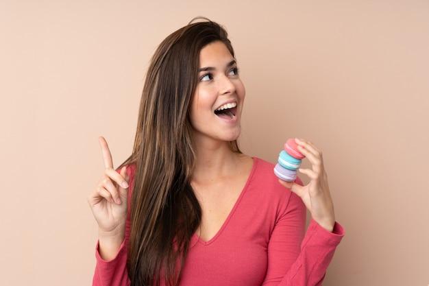 La ragazza dell'adolescente sopra la parete isolata che tiene i macarons francesi variopinti e che intende realizzare la soluzione