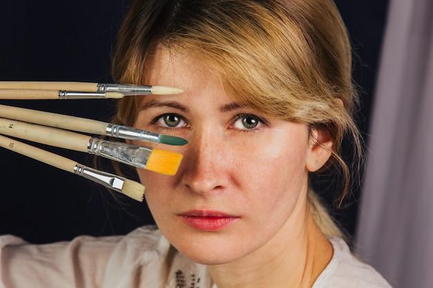 La ragazza dell'artista in un abito bianco chiaro, dipinge un quadro su tela in officina. il giovane studente usa pennelli, tele e cavalletti. lavoro creativo per bambini e adulti.