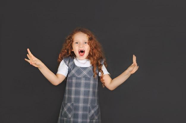 La ragazza della scuola che mostra l'espressione facciale di emozione di avversione e la mano si alzano per fermarsi o proteggere