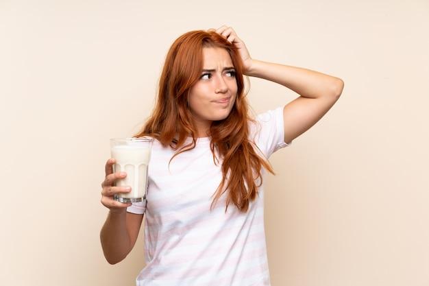 La ragazza della testarossa dell'adolescente che giudica un bicchiere di latte sopra ha isolato avere dubbi e con l'espressione confusa del fronte