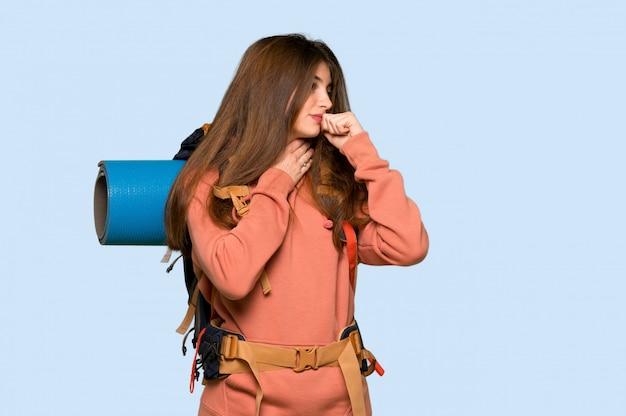 La ragazza della viandante sta soffrendo con la tosse e ritenendo cattiva su fondo blu