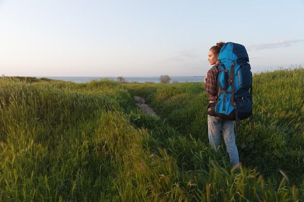 La ragazza della viandante sta viaggiando con uno zaino sui precedenti del paesaggio