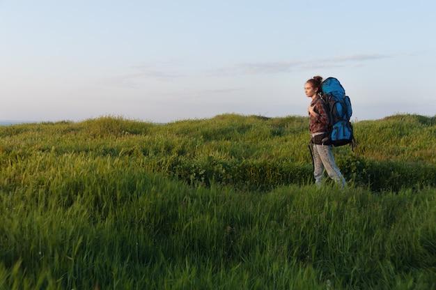 La ragazza della viandante sta viaggiando con uno zaino sul paesaggio