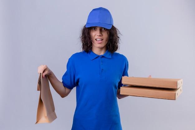La ragazza delle consegne in uniforme blu e cappuccio che tiene le scatole della pizza e il pacchetto di carta è uscita e sorpresa in piedi sul bianco