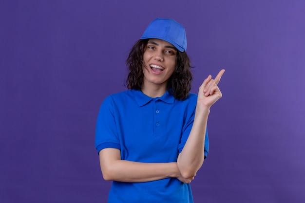 La ragazza delle consegne in uniforme blu e cappuccio si ricorda di non dimenticare la cosa importante sorridendo allegramente in piedi sul viola isolato
