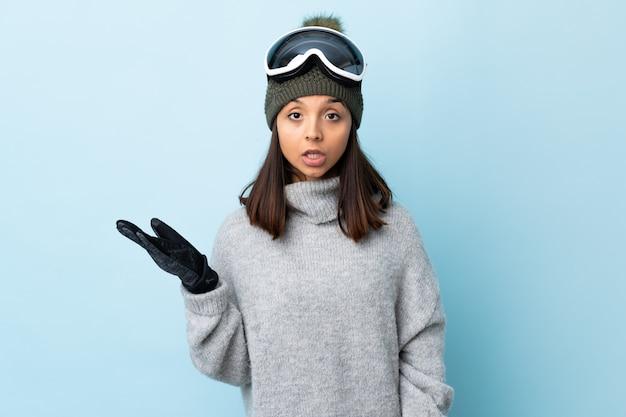 La ragazza dello sciatore della corsa mista con i vetri di snowboard sopra la parete blu isolata che fa i dubbi gesticola