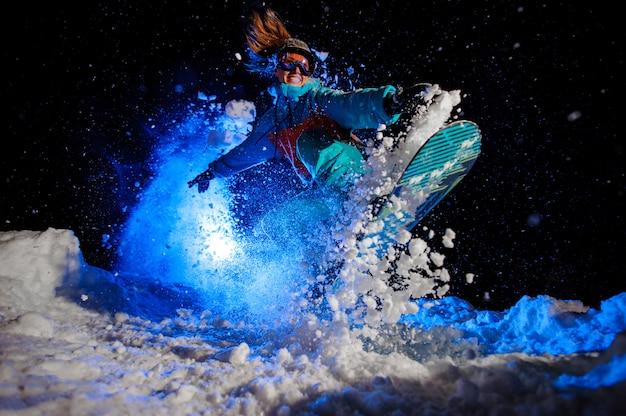 La ragazza dello snowboarder vestita in abiti sportivi arancioni e blu esegue i trucchi sulla neve