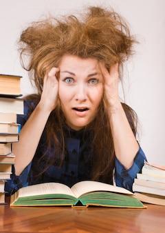 La ragazza dello studente con i libri mostra l'espressione di panico