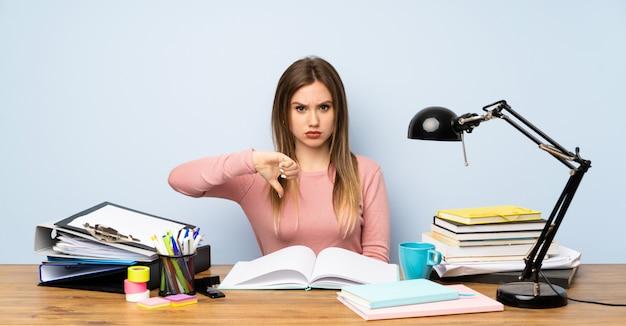 La ragazza dello studente dell'adolescente nella sua stanza che mostra il pollice giù firma
