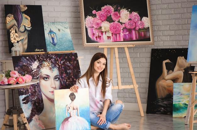La ragazza dello studente della scuola d'arte con la sua pittura sulla mostra mostra in uno studio
