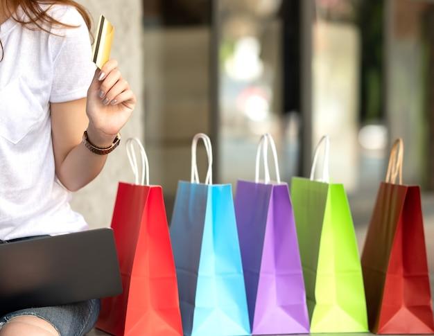 La ragazza di acquisto della carta di credito a disposizione con i sacchetti della spesa ed il computer portatile hanno messo sul pavimento.