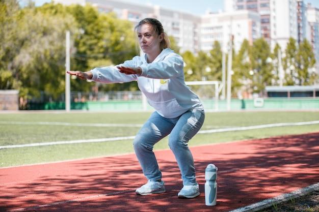 La ragazza di bellezza di squatting.young fa gli esercizi allo stadio