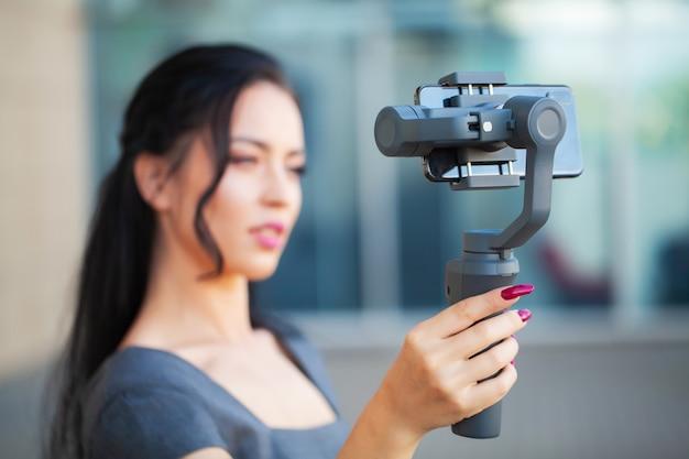 La ragazza di blogger gira un video su come viaggiare su uno stabilizzatore elettronico.