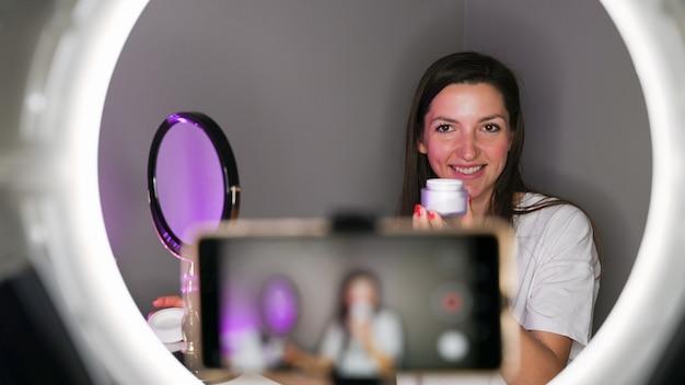 La ragazza di blogger mostra la crema per la pelle.