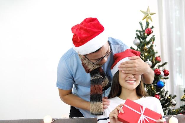 La ragazza di chiusura di sorpresa felice del giovane osserva con le mani con il contenitore di regalo nelle feste di natale.
