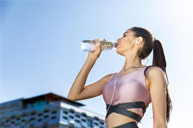 La ragazza di forma fisica che ascolta una musica beve l'acqua