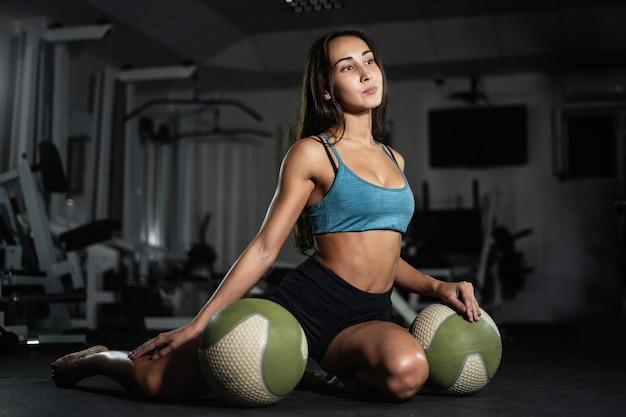 La ragazza di forma fisica posa con palle in palestra