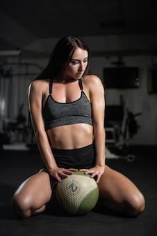 La ragazza di forma fisica posa con una palla in palestra