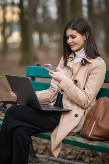 La ragazza di modello castana tenera lavora al computer portatile e al telefono fuori nel parco