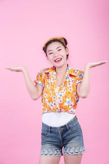 La ragazza di modo si agghinda con i gesti di mano su un fondo rosa.