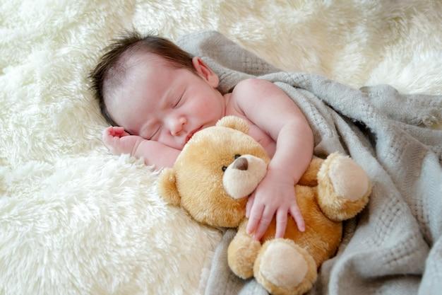 La ragazza di neonato sveglia dorme con un orsacchiotto del giocattolo