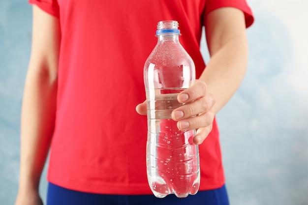 La ragazza di sport tiene la bottiglia con acqua, fine in su