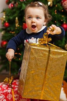 La ragazza di tddler con i regali si avvicina all'albero di natale.