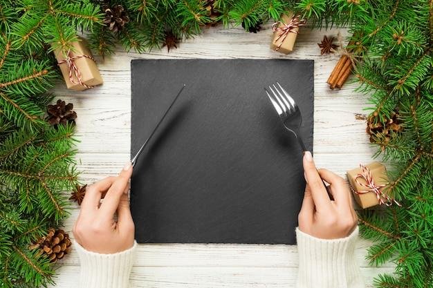 La ragazza di vista superiore tiene la forchetta e il coltello in mano ed è pronta da mangiare. piatto quadrato vuoto in ardesia nera. concetto di piatto cena vacanza con decorazioni di capodanno