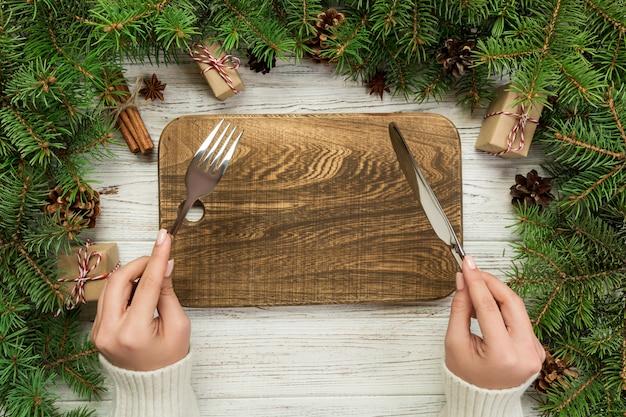 La ragazza di vista superiore tiene la forchetta e il coltello in mano ed è pronta da mangiare. piatto rettangolare di legno vuoto sul bordo di legno. concetto di piatto cena vacanza con decorazioni di natale