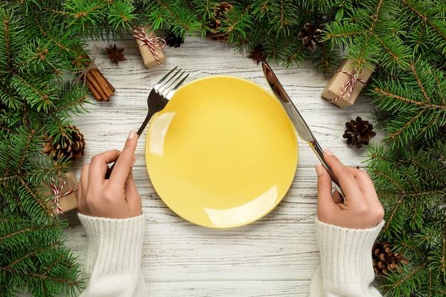 La ragazza di vista superiore tiene la forchetta e il coltello in mano ed è pronta da mangiare. piatto rotondo in ceramica vuota su sfondo di legno di natale.