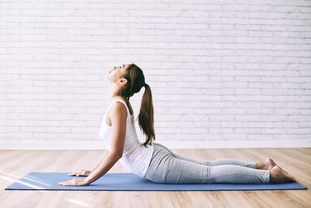 La ragazza di yoga che fa il cobra asana come la sua mattina si esercita a casa