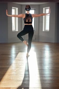 La ragazza di yoga di mattina che fa l'allungamento si esercita nella stanza per pilates