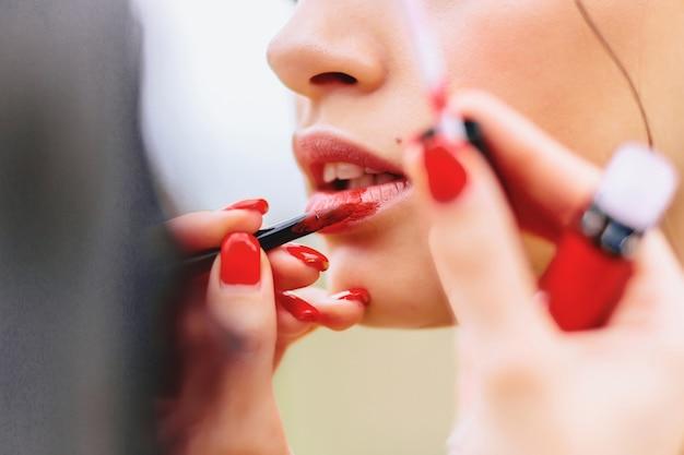 La ragazza dipinge le labbra in rosso sulla strada
