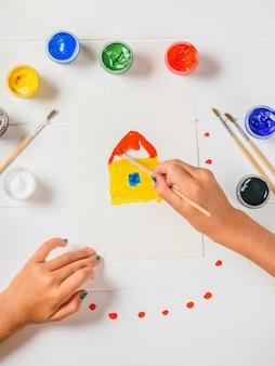 La ragazza dipinge una casa su uno strato su una tavola di legno bianca. disteso.