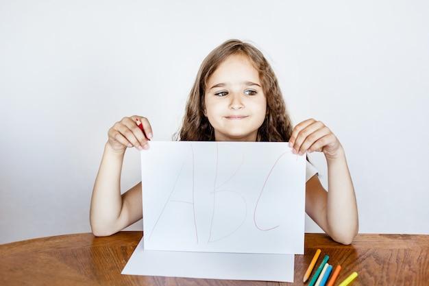 La ragazza disegna in un taccuino, scrive lettere, matite colorate, lezioni a casa, formazione online, sviluppo dell'intelligenza mentale