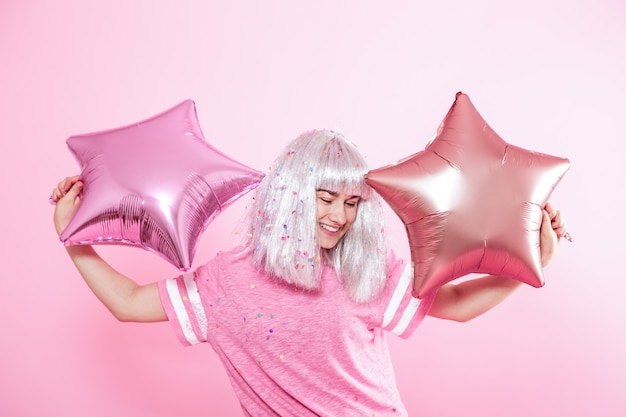 La ragazza divertente con i capelli d'argento dà un sorriso ed emozione. giovane donna o ragazza teenager con palloncini e coriandoli