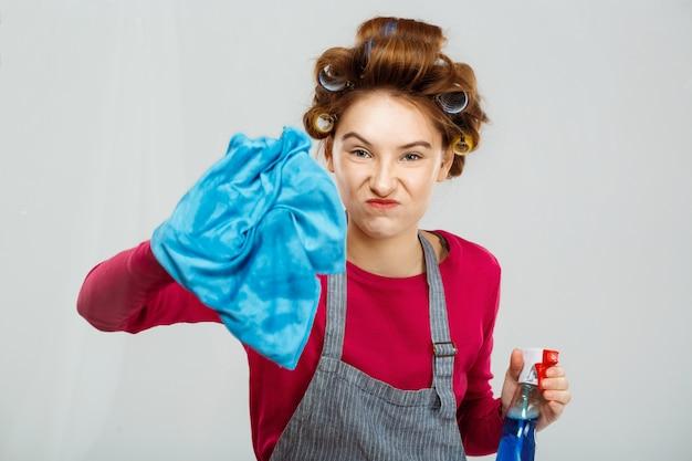 La ragazza divertente pulisce la finestra con lo spruzzo della tenuta dell'asciugamano