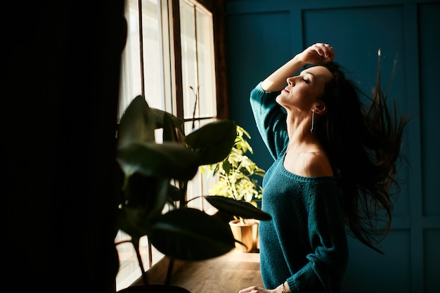 La ragazza è felice di essere al sole la mattina nel suo appartamento