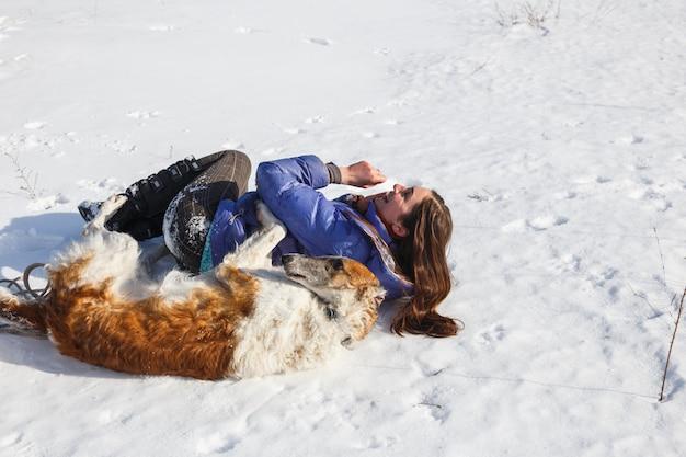 La ragazza e il levriero russo sguazzano nella neve