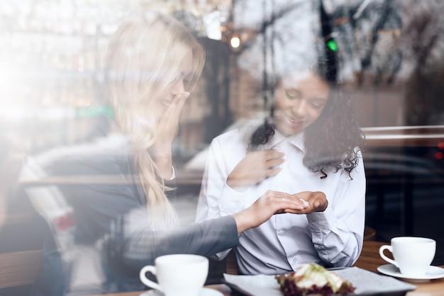 La ragazza e il mulatto sono seduti al bar e bevono caffè.
