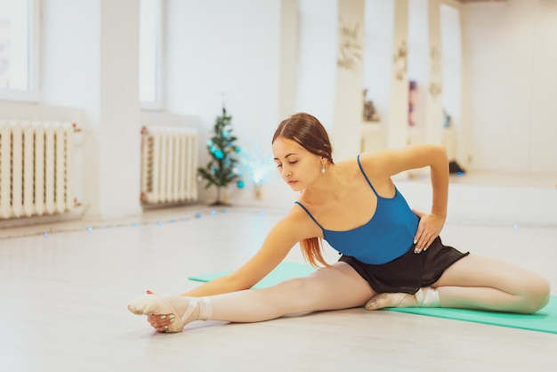 La ragazza è impegnata in ginnastica, facendo stretching in palestra