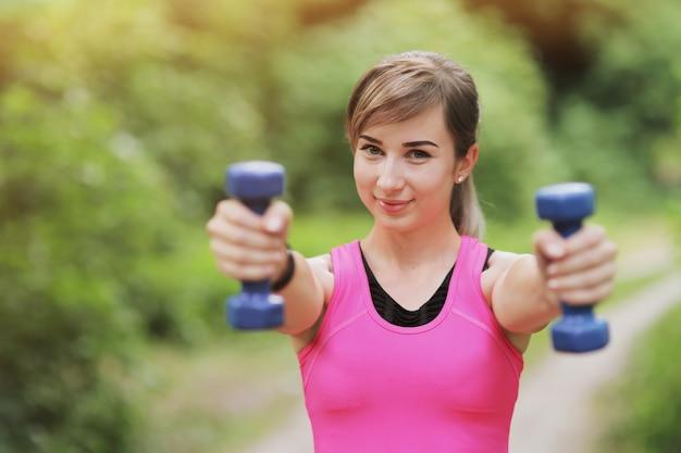 La ragazza è impegnata in sport con pesi nella foresta naturale. vita in forma sana